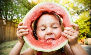 A young girl eating a full slice of watermelon.